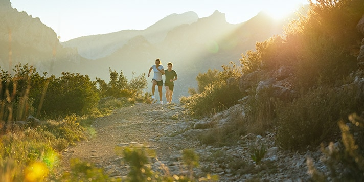 Two runners ascend a mountain trail, with hills behind them.