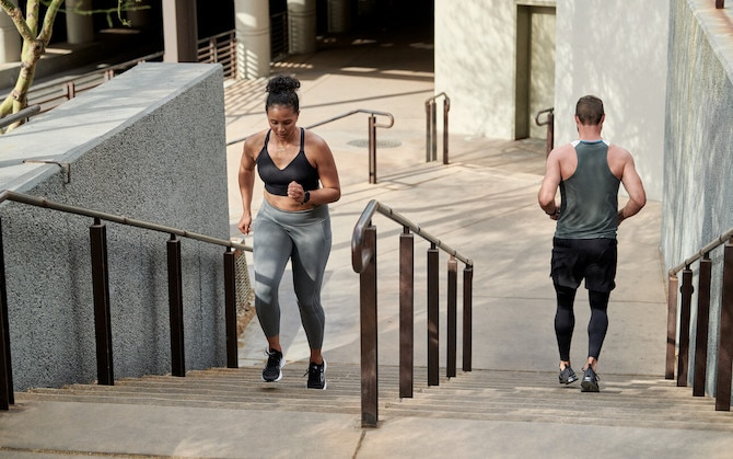 Two runners go up and down a set of stairs, respectively, in an urban environment.