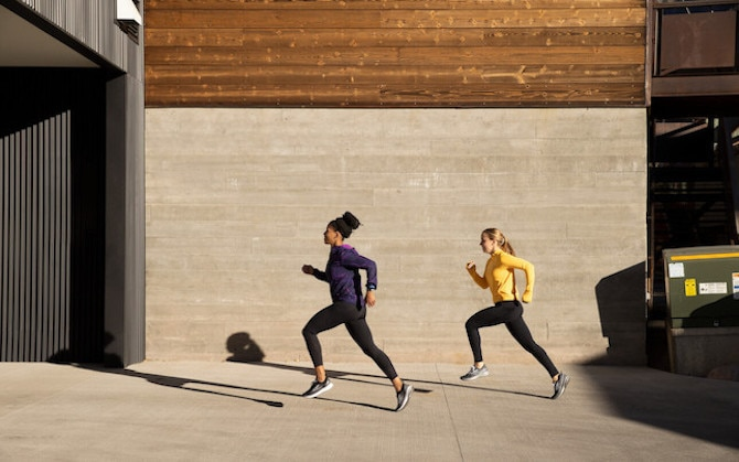 Two runners sprint on a sidewalk during high-intensity interval training.