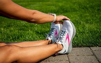 Women reaching for her toes wearing the ricochet 3 shoes