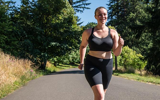 Women running on a paved trail in a Dare Racerback run bra