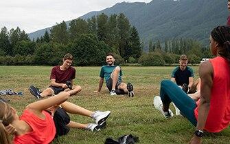 Athletes sitting in circle stretching