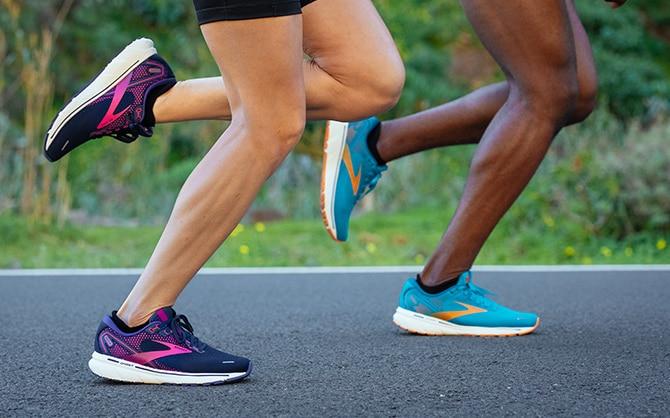 Die Läufer sind mitten im Schritt und tragen Brooks-Schuhe mit weicher DNA LOFT-Dämpfung