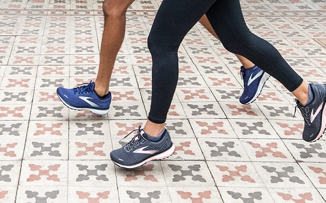 Close-up of two runners' legs running on a surface paved with patterned tiles.