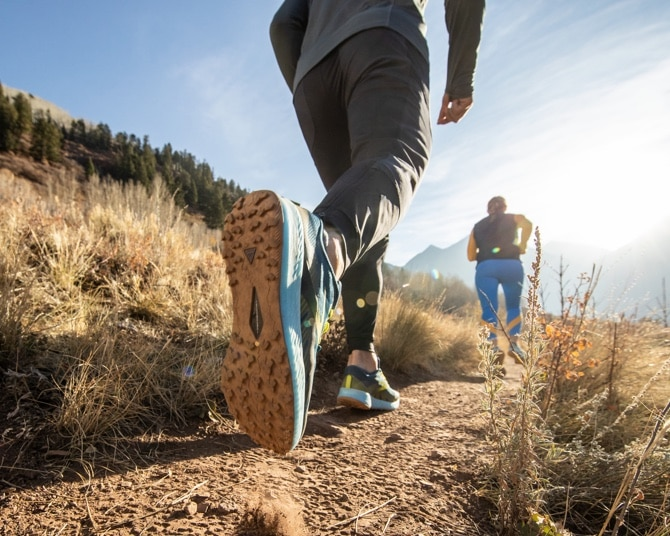two runners walking down a trail in the mountains