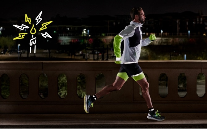 Side view of a runner running on a road at night while wearing reflective gear