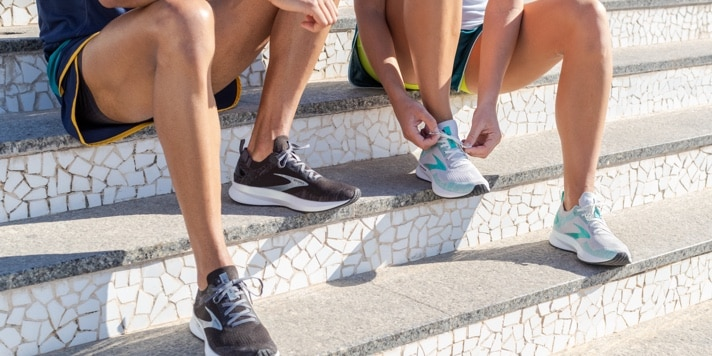 Close-up of two runners' legs as they tie their shoes on a set of steps.