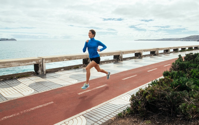 Woman running on a trail on the coast
