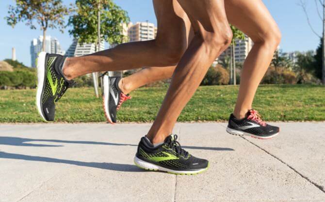 Runners are mid-stride wearing Brooks shoes with soft DNA LOFT cushioning