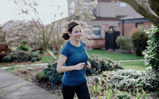 Runner running by a tennis court