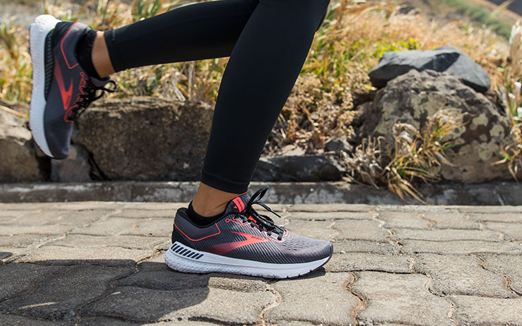 A runner strides along a paved road wearing a pair of grey and red Transcend shoes.