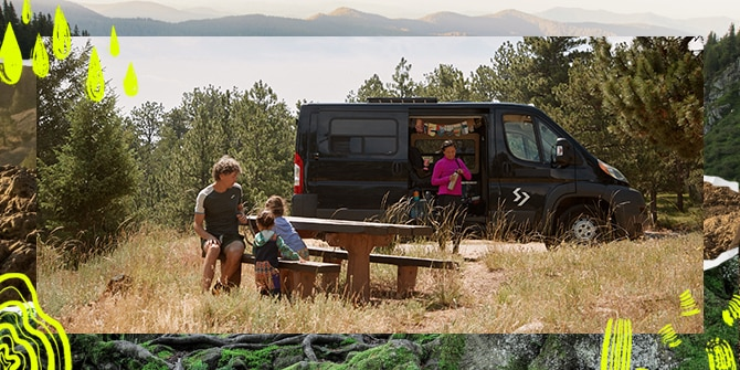 Ein Mann sitzt mit zwei Kindern an einem Picknicktisch, während eine Frau neben dem Camper steht