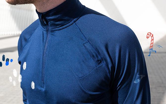 A closeup shot of a man wearing a navy Brooks half-zip.