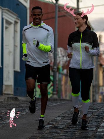 A man and woman in Brooks Run Visible reflective gear run at night.