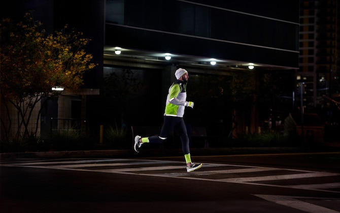 Side view of two runners running on a road at night while wearing reflective gear.