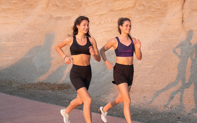 Two smiling runners run on a walkway in front of a rock cliff side.