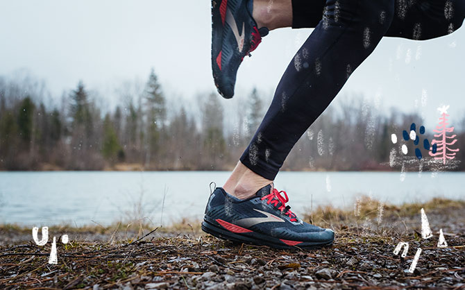 A runners legs in mid stride shown running on a wet, rocky trail next to a river.