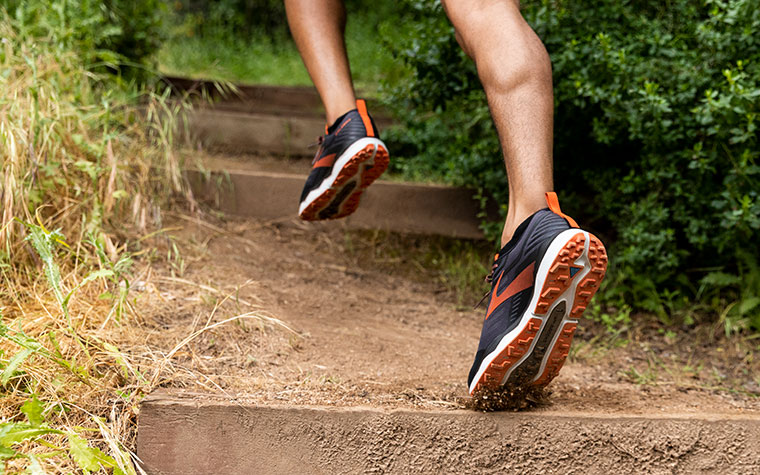 Close-up of runner's feet in the Caldera, ascending stairs on a dirt trail.