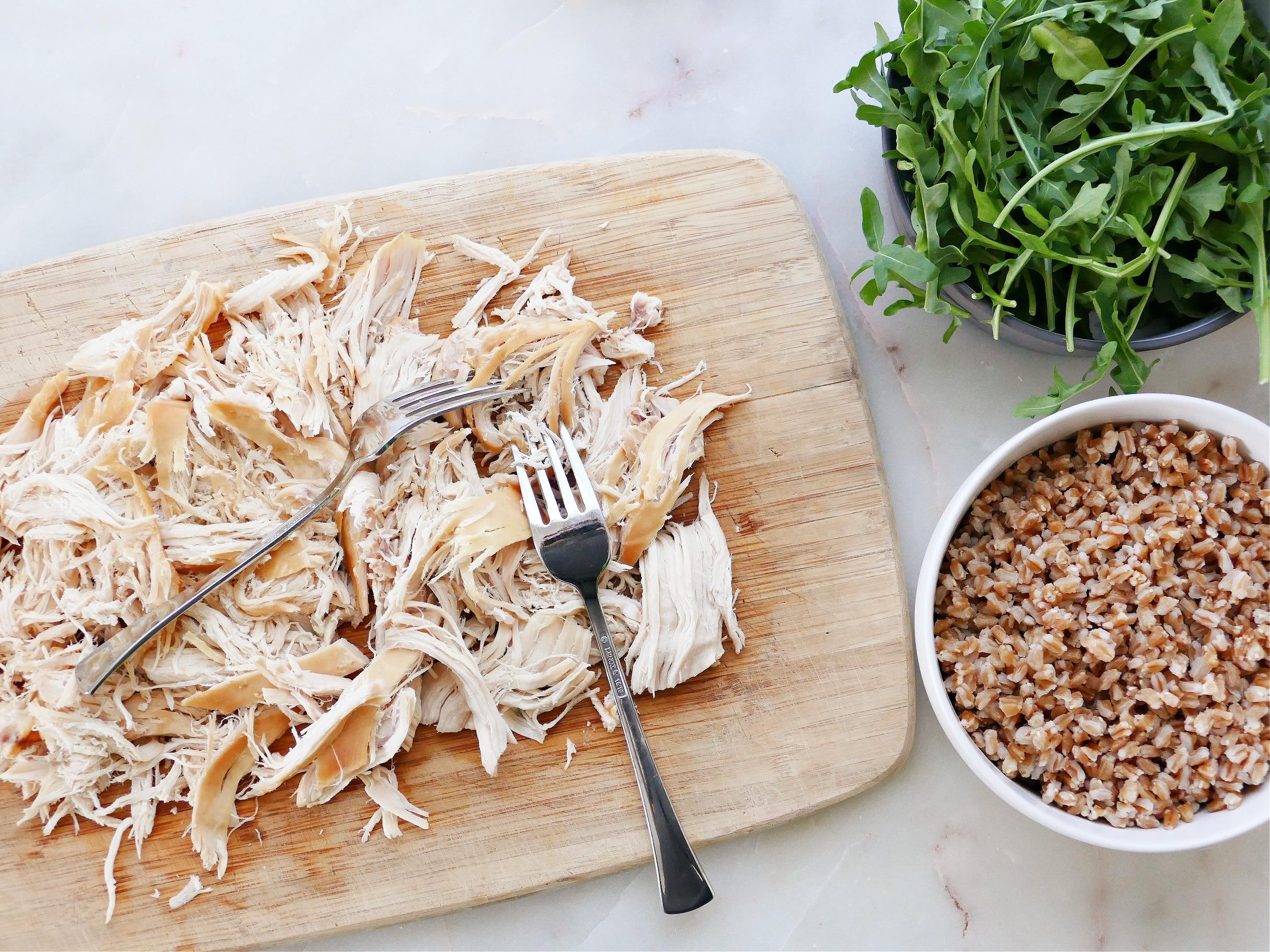 a cutting board with shredded chicken