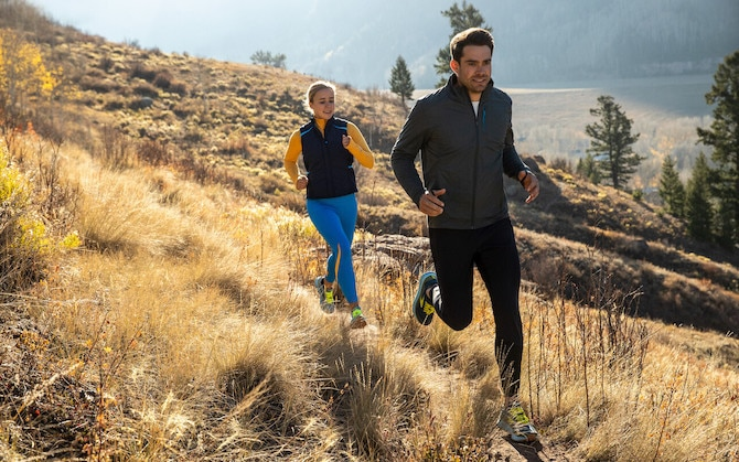 Two runnners on a meadow trail