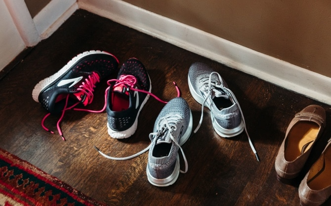 Three pairs of shoes near the front door of a house.