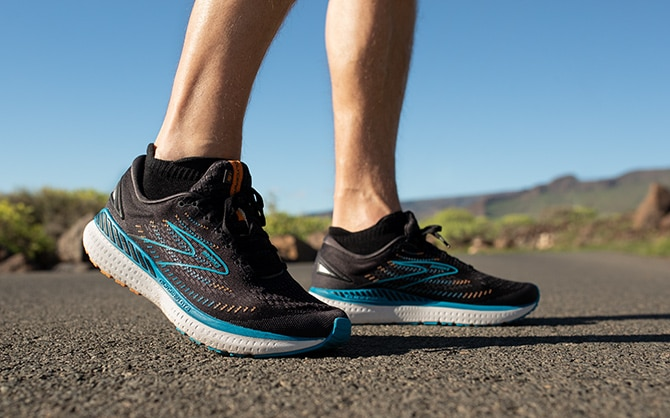 Two pairs of Brooks road-running shoes are placed side by side.