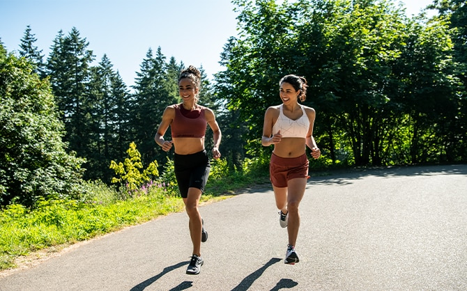Two women running down a path