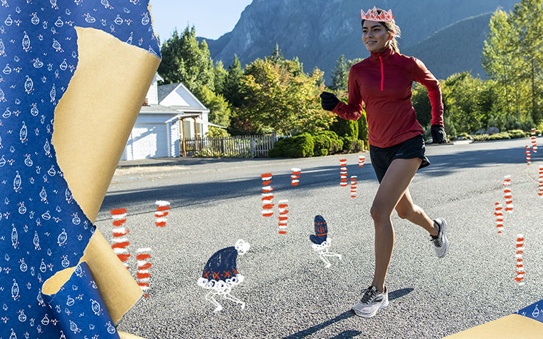 A runner wearing a read long sleeve half zip and shorts runs on a road with mountains in the background.