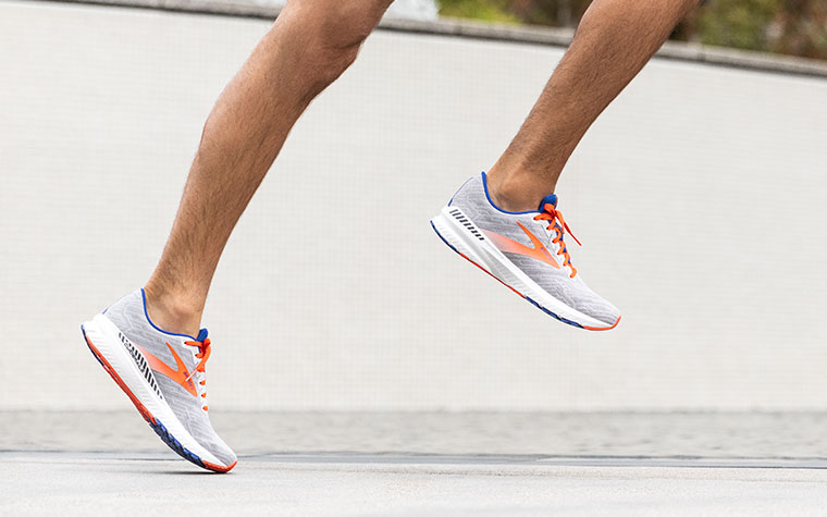 Close-up of a runner's legs mid-stride, wearing grey and orange Ravenna shoes in front of a grey wall.