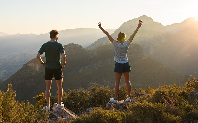 Two runners, one with hands on his hips and the other with hands raised high in celebration, look out at a picturesque mountain landscape.