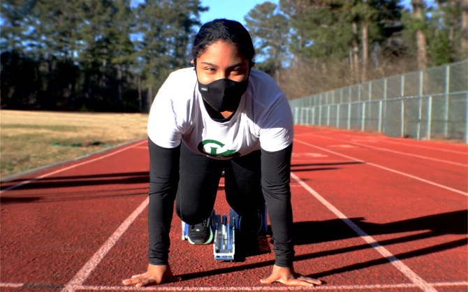 Women on a track with her feet in race blocks