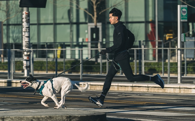 Man and his dog sprinting across a street.