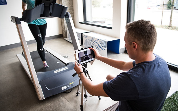 A man uses a tablet to observe a runner who is running on a treadmill in a lab.