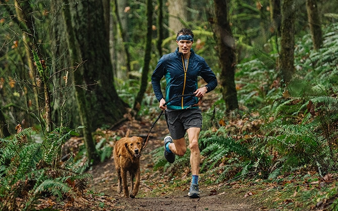 Man running with his dog through the forest.