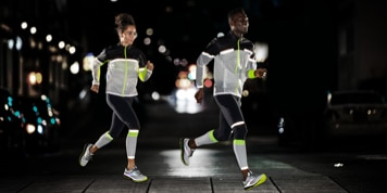 Two runners wearing high-visibility tights and jackets train in the dark.