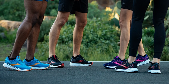 A group shot of runners on a bench, with bright new Brooks running shoes.