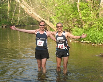 Richard and Zander standing in a river after a race.