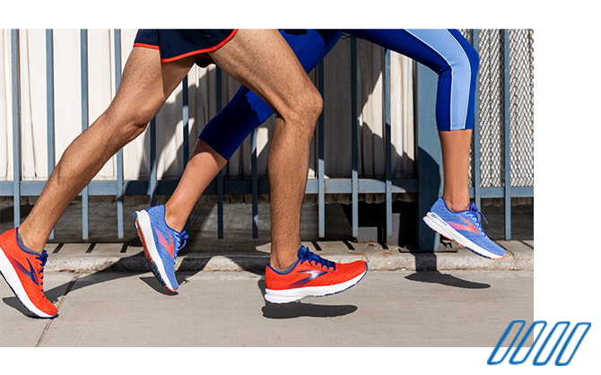 Close up photo of the legs of two runners wearing Brooks Ravenna shoes with GuideRails technology.