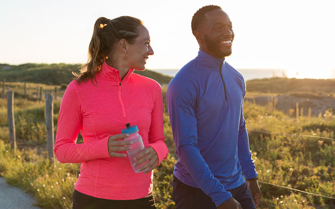 Two runners smiling on a trail