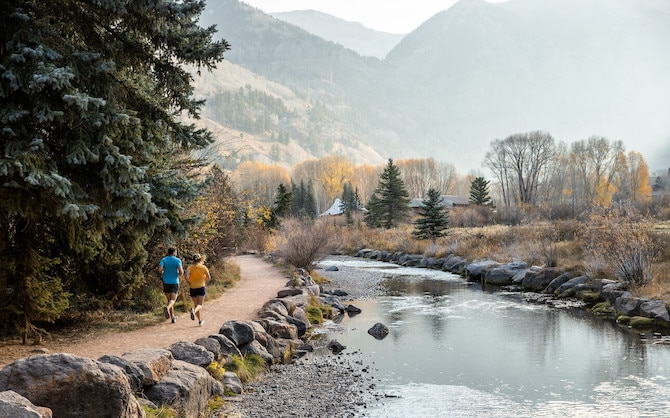 Two runners on a trail next to a river