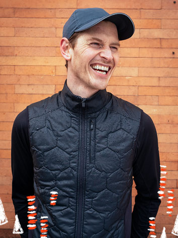 A smiling man wearing a hat, vest, and long sleeve shirt poses in front of a brick background.