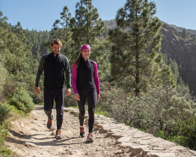 A man and a woman walking next to each other on trail
