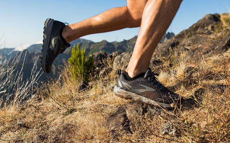 Nahaufnahme des Läufers mit Divide beim Aufstieg an einem grasbewachsenen Berghang.
