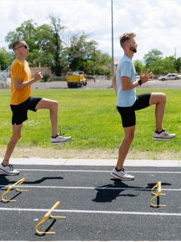 Two men doing warm-ups on the track