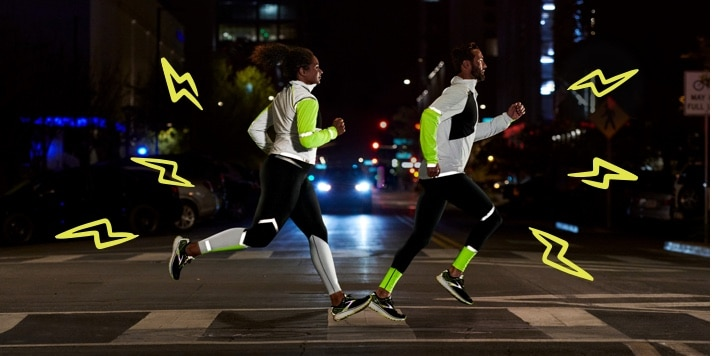 Side view of two runners running on a road at night while wearing reflective gear