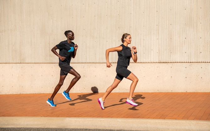 Two runners with a concrete wall behind them