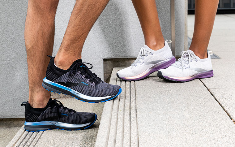 Two runners stand on concrete steps, one wearing black and blue Ricochet shoes, one wearing white and purple Ricochet shoes.