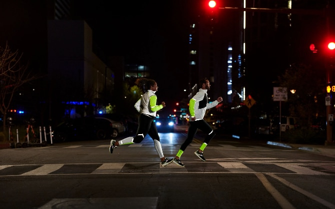 Side view of two runners crossing a street in the dark