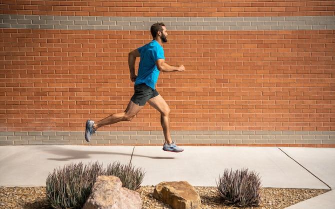 Man running by a brick wall