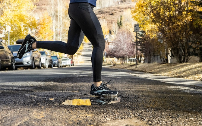 Woman running across a road